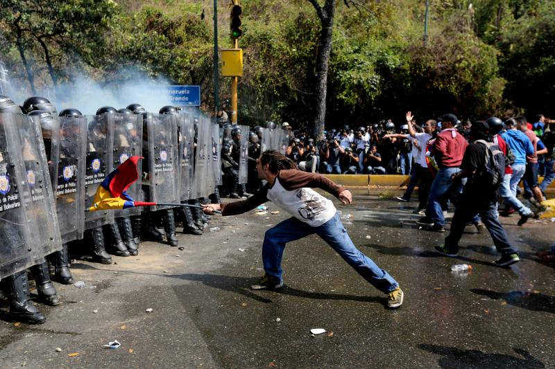 A demonstrator uses a Venezuelan flag to strike at a line of Bolivarian National Police officers in riot gear, during clashes at a anti-government protest in Caracas, Venezuela, Wednesday, March 12, 2014. A university student has died and a number of othe