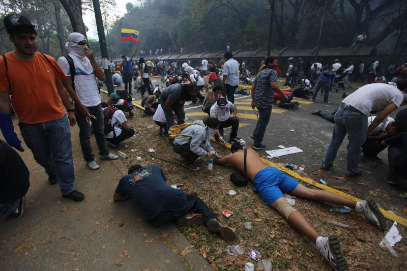 Demonstrators lie on the ground overwhelmed by tear gas fired by Bolivarian National Police officers, during clashes at an antigovernment protest in Caracas, Venezuela, Wednesday, March 12, 2014. According to local authorities, several deaths have been re
