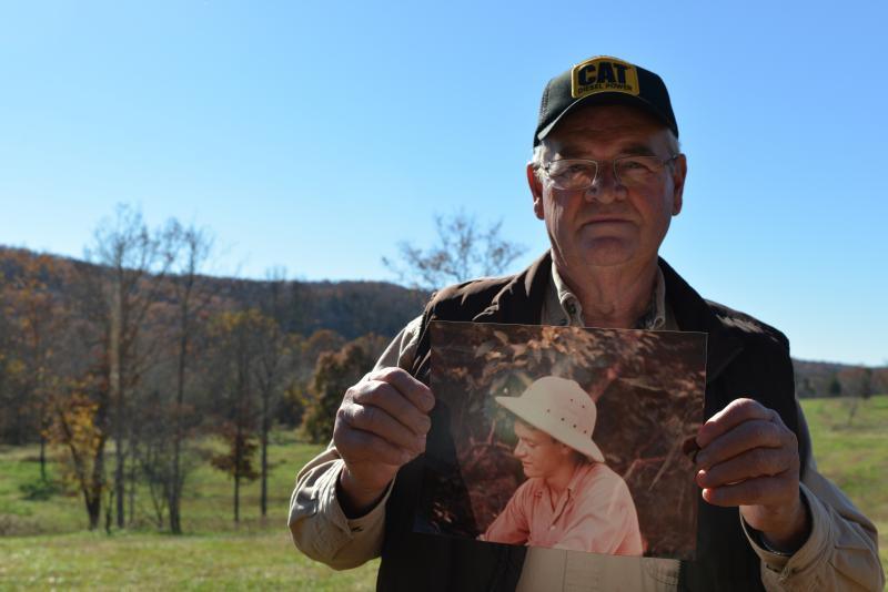 Phil Moss holds a picture of his younger self as a river guide on the Current River while he stands on his private easement in the Ozark National Scenic Riverways.  Moss comes from a family of river guides and began guiding himself at the age of 12.