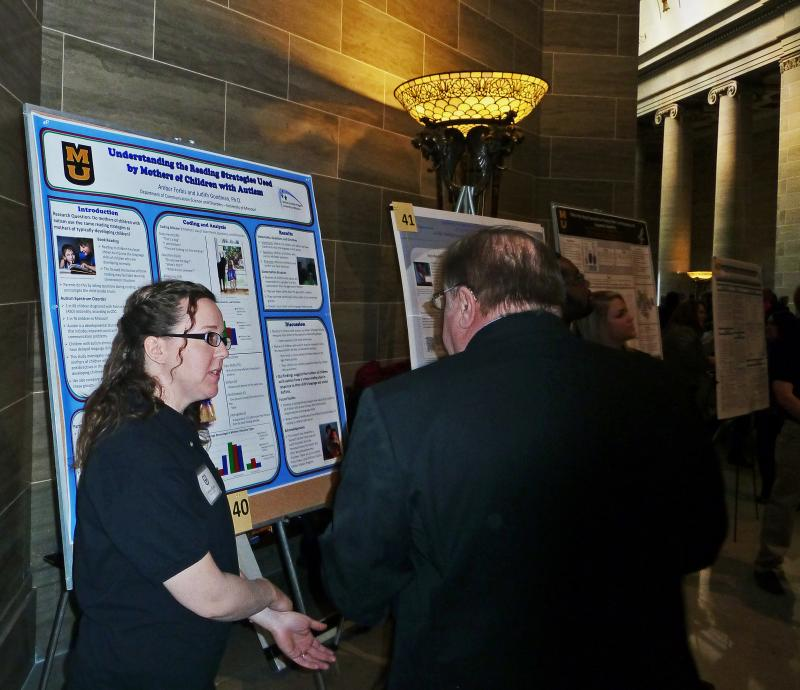 University of Missouri senior Amber Forbis presents a poster about her work to a spectator of Undergraduate Research Day at the Missouri State Capitol on Tuesday, March 4, 2014.