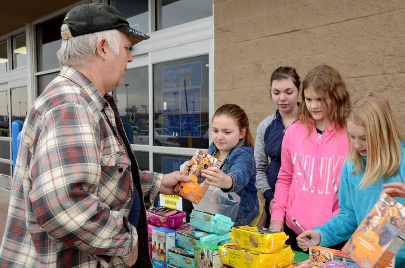 Brayden Dodds hands a box of Peanut Butter Sandwich cookies to retired Army Sgt. Ronald Stephenson as, from left, Izzy Sullivan, Maddie Renner and Ainsley Benson stand nearby at a Girl Scout Cookie booth sale Feb. 22 in front of the Walmart on Conley Road