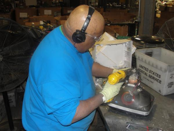 An employee at EPC in Earth City, Missouri dismantles a computer monitor for recycling.