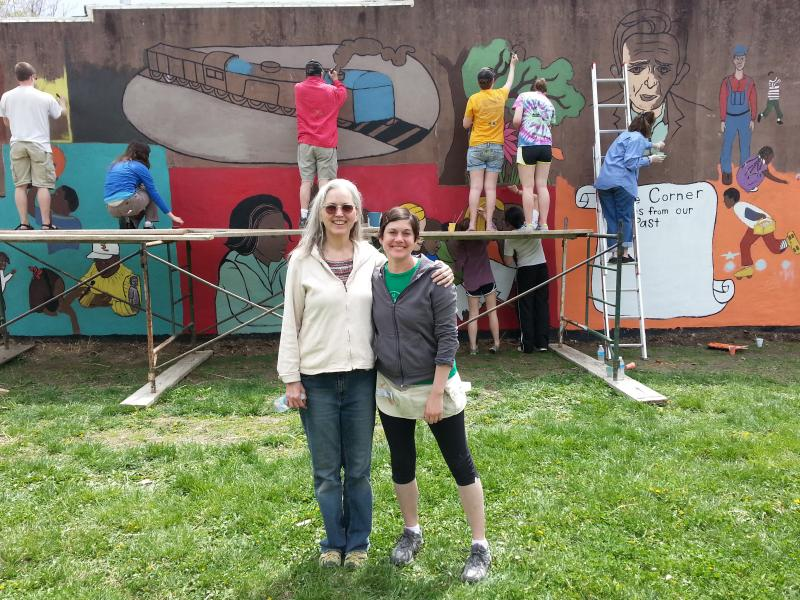 Starbuck and Pfannenstiel pose in front of the mural as residents continue painting.