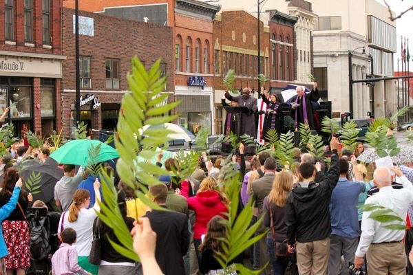 Members of the crowd raise palm branches at the ecumenical Palm Sunday service on April 13, 2014 in downtown Columbia.