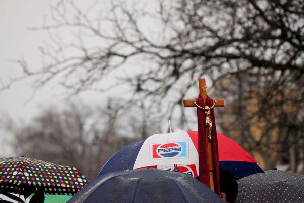 A crucifix is held above the sea of umbrellas at the Blessing of the Palms in downtown Columbia on April 13, 2014.