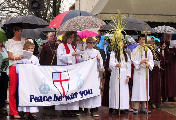 A group from Calvary Episcopal Church holds a banner at the ecumenical Palm Sunday service on April 13, 2014.