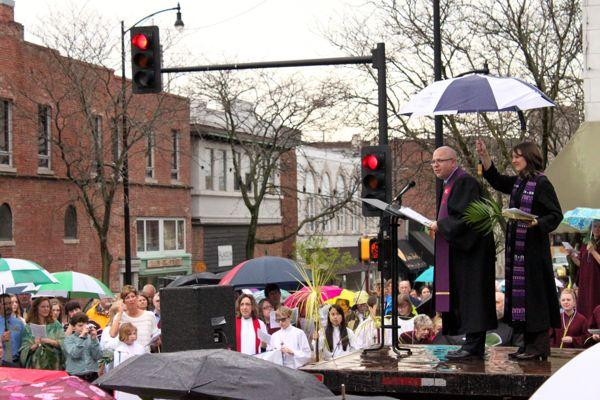 The Rev. Brad Stagg of First Christian Church leads a prayer, as the Rev. Carol McEntyre of First Baptist Church holds an umbrella.