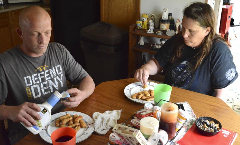 Bobby and Christie Clark share a late afternoon snack of frozen chicken fingers inside their Sedalia, Mo., home on Monday, April 21, 2014. Christie and her two kids receive food stamps, but Missouri denies Bobby access because of his drug felony. Missouri