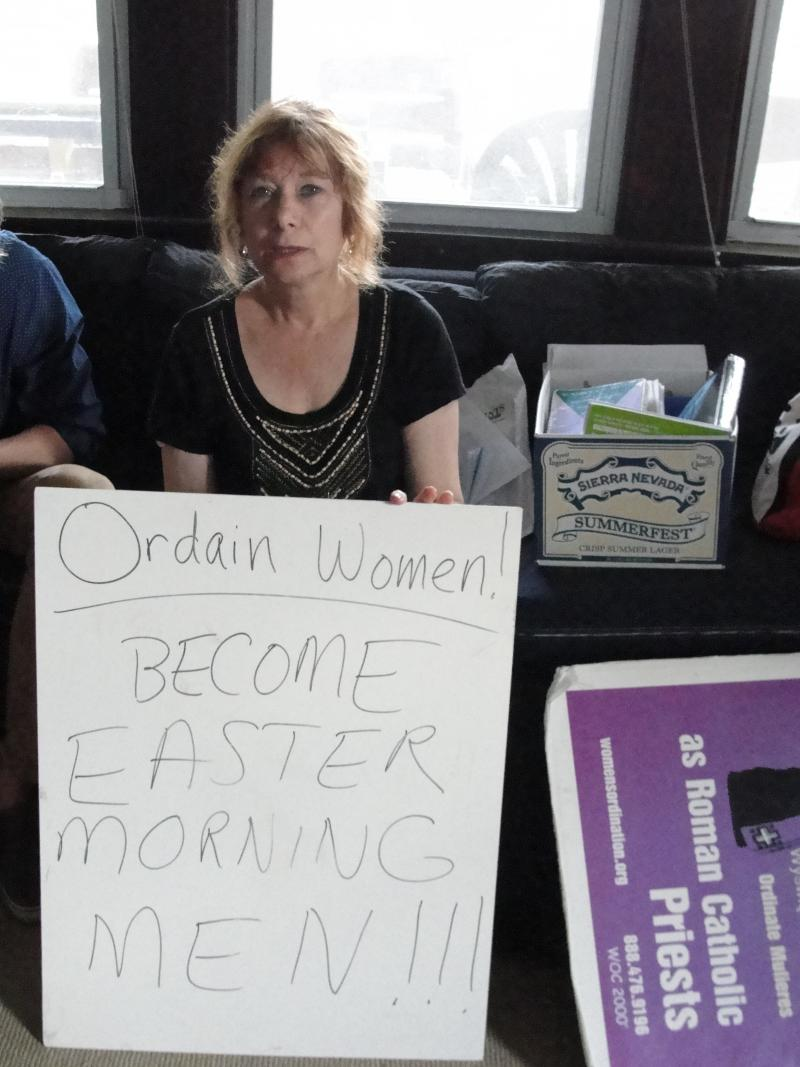 Female Roman Catholic priest Janice Sevre-Duszynska displays a sign she used in protest of the exclusion of women from the priesthood. Sevre-Duszynska visited St. Francis House in Columbia, Missouri on May 28, 2014, to say mass and screen the documentary
