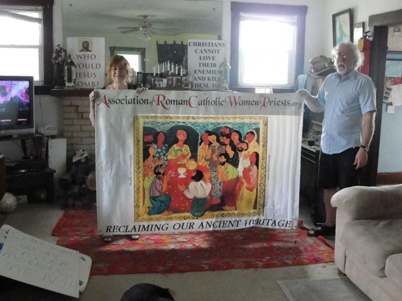 Female Roman Catholic priest Janice Sevre-Duszynska and St. Francis House founder Steve Jacobs hold a sign promoting the Roman Catholic Women Priests. Sevre-Duszynska visited St. Francis House in Columbia, Missouri on May 28, 2014, to say mass and screen