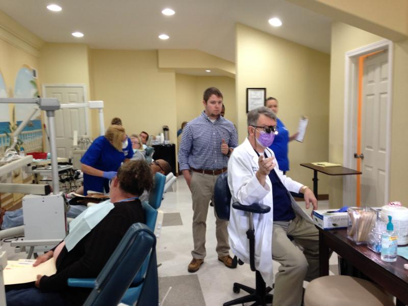 Dr. Bill Kane (right) directs some church volunteers and dental assistants.