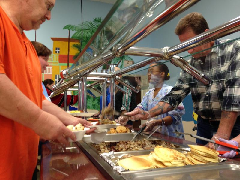 Church volunteers prepare a free brekfast for clinic patients before they have their teeth removed.
