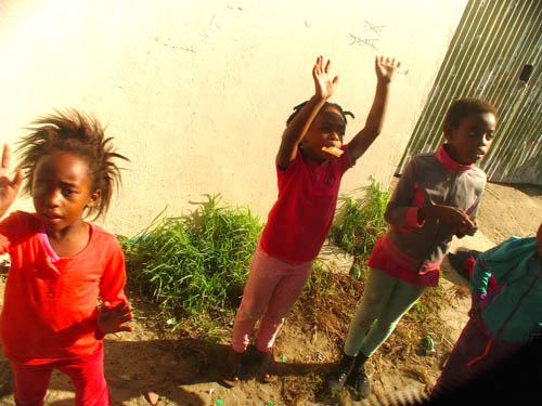 (Kids waving): Children greet visitors to the Masiphumelele township outside of Cape Town. Twenty years after ushering in democracy, South Africa's citizens suffer from one of the world's widest gaps between rich and poor.