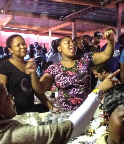 At Mzoli's, local residents of the Guguletu Township begin an impromptu celebration that soon catches on to other tables. People wait in line for hours for barbecued food and then relax to music.