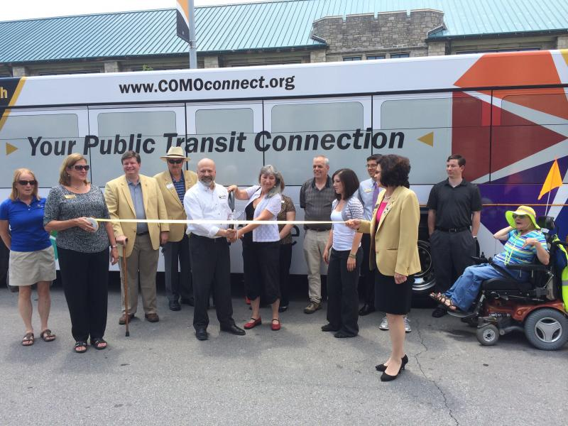 Columbia Councilwoman Barbara Hoppe and COMO Connect Multi-Modal Manager Drew Brooks cut the ribbon in front of a bus with the new COMO Connect logo in Columbia, Mo Tuesday afternoon.