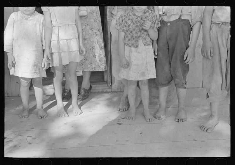 Feet and clothing of family of sharecropper, cut-over farmer of Mississippi bottoms. Osage, Mo. (May 1938)