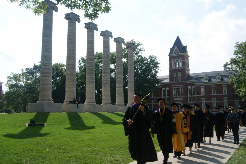 The procession to Chancellor R. Bowen Loftin's inauguration passes the columns.