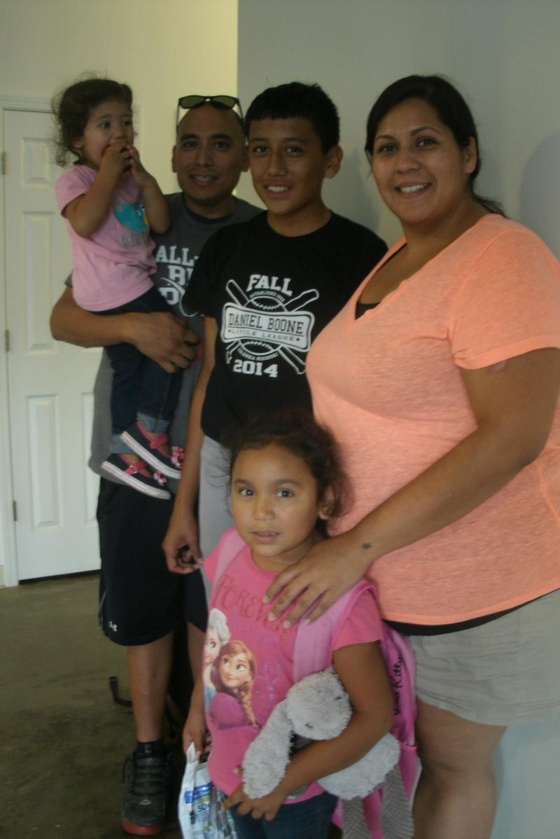 Lupe Ortiz (at right) was at El Centro Latino recently to pick up her son Christian (center.) Also there were Lupe's husband Carlos and daughters Analynn and Charlotte (standing.)