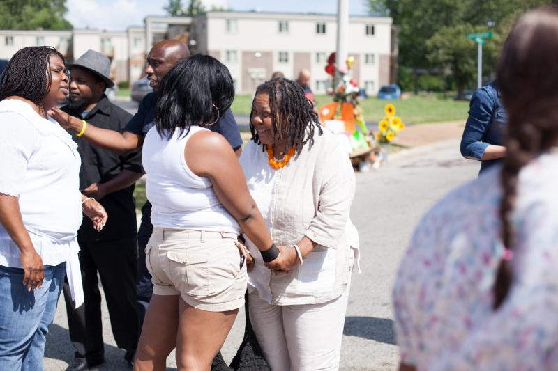 Ferguson residents greet and console each other outside the Canfield Green apartments on August 14.