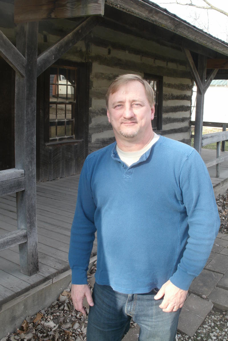 Novinger Mayor and local pastor Jeff Dodson stands in front of the town's log cabin museum, which formerly housed the town's founder John C. Novinger and his family.
