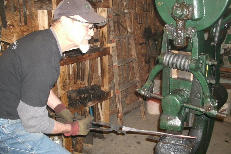 Working at his trip hammer, Bernard Tappel flattens steel before returning it to the forge..