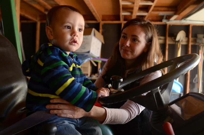 "Danielle Geurts helps her 1-year-old son Emmett off a tractor at their Columbia, Mo. home. While nursing Emmett, Geurts donated her extra breast milk to Sarah Cranston after they both posted to the milk sharing facebook pag, ""Human Milk 4 Human Babies."""