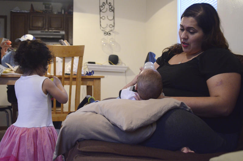 Lupe Ortiz holds her son Jonah for thier evening breast milk feeding. Ortiz uses Facebook pages that connect breast milk donors to recipients. Jonah drinks donated breast milk while he's at daycare, and Ortiz's in the evening.