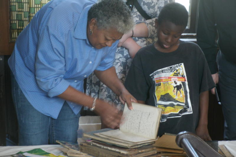 Sandra Enyard and her grandson Javon inspect historic diaries at Glasgow, Missouri's Campbell Chapel AME Church. She grew up in the now preserved chapel and is featured in this episode of Thinking Out Loud.