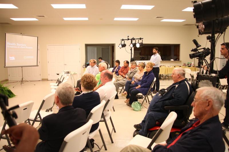 Audience members listen to the panel answering questions about health care access.