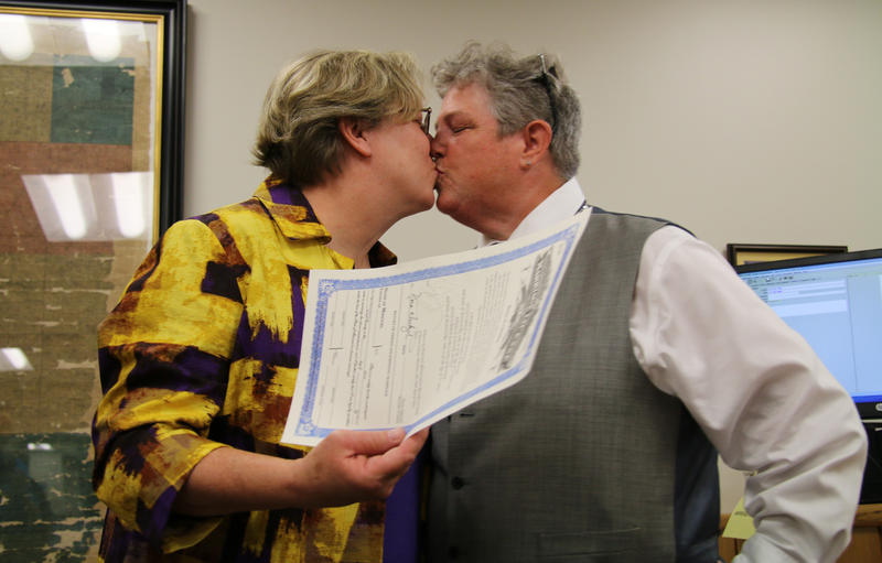 Laura Zinszer (left) and Angie Boyle share a kiss after being issued the first marriage license in Columbia on June 26.