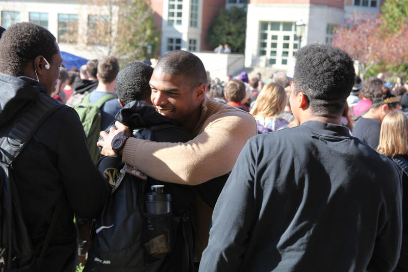 Michael Sam embraces a friend after the announcement of Wolfe's resignation.