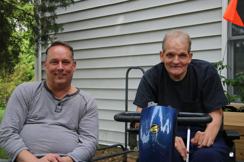 Chuck Graham, left, is wearing a gray and white thiny striped long-sleeved shirt and sits in a manual wheelchair. His brother Drew, right, is wearing a black T-shirt and sits in a bright blue power scooter.
