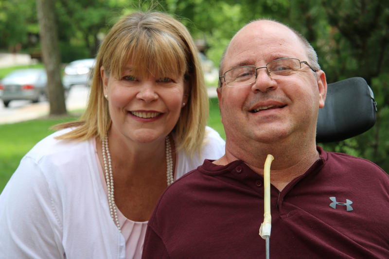 Leslie Anderson stands over the shoulder of Max Lewis wearing a pink blouse amnd white cardigan. She has blonde hair. Max Lewis, right, sits in a power wheelchair wearing glasses and a red shirt. They both smile into the camera.
