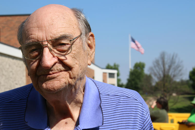 Jack Gouverneur stands looking into the camera. He is 86 years old, has many wrinkles and is balding. He wears a blue and black striped polo. There is an American flag flying over his left shoulder.
