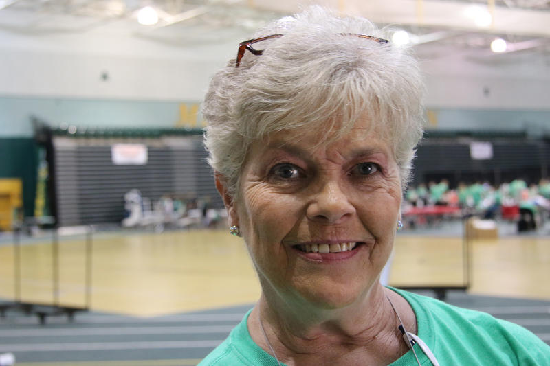 Terri Rose smiles into the camera. She is an older woman with short, white hair. She is wearing a green, MOMOM volunteer shirt and her glasses rest on the top of her head.