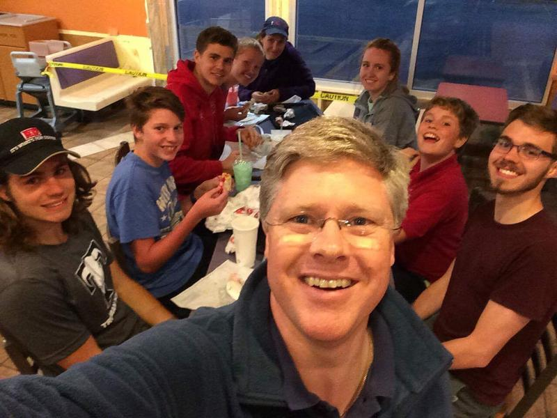 A selfie. Simon McKeown stands in front of his family in a dark blue shirt and glasses. Behind him are his seven children and wife. His oldest son Jonah sits bottom right - has a beard, glasses and a wears a maroon t-shirt.