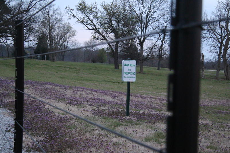 "Fencing surrounds a patch of grass that used to be a neighborhood in the center of Herculaneum, Missouri. A sign in the grass reads, ""No Trespassing. Lead Contamination."""
