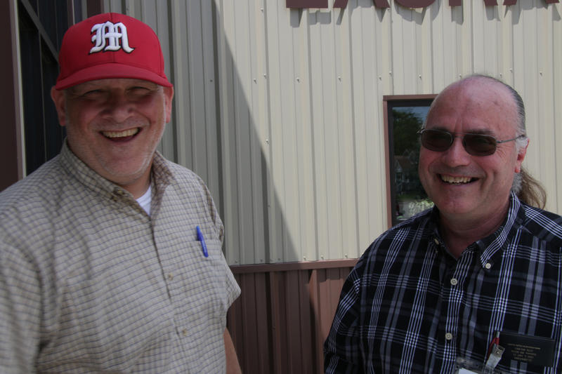 Tad Dobyns, left, and Phil Iman, right, stand in front of the Help Center – a beige building. Dobyns wears a checkered shirt and a bright red baseball cap. Iman, who has a long ponytail, wears glasses and a plaid shirt.