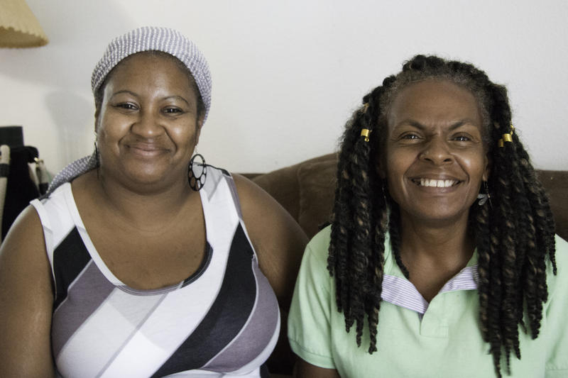 Carolyn Lewis, left, wears a black, white and gray striped shirt and smiles into the camera. Sheila Artis, right, wears a green polo shirt and smiles broadly.