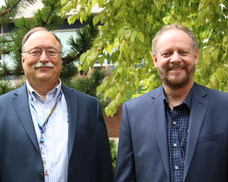 Dr. John Dane, left, wears glasses, a dark blue suit and a white and blue-checkered shirt. Gary Harbison, right, has a full beard and wears a dark blue shirt and suit.