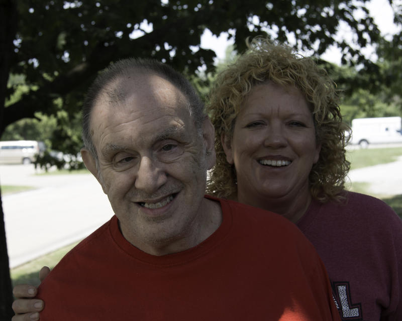 Darrell Watts, left, has short hair and wears a red shirt. He stands in front of his sister Lisa Harrison, right, who has curly blonde hair and wears a pink shirt.