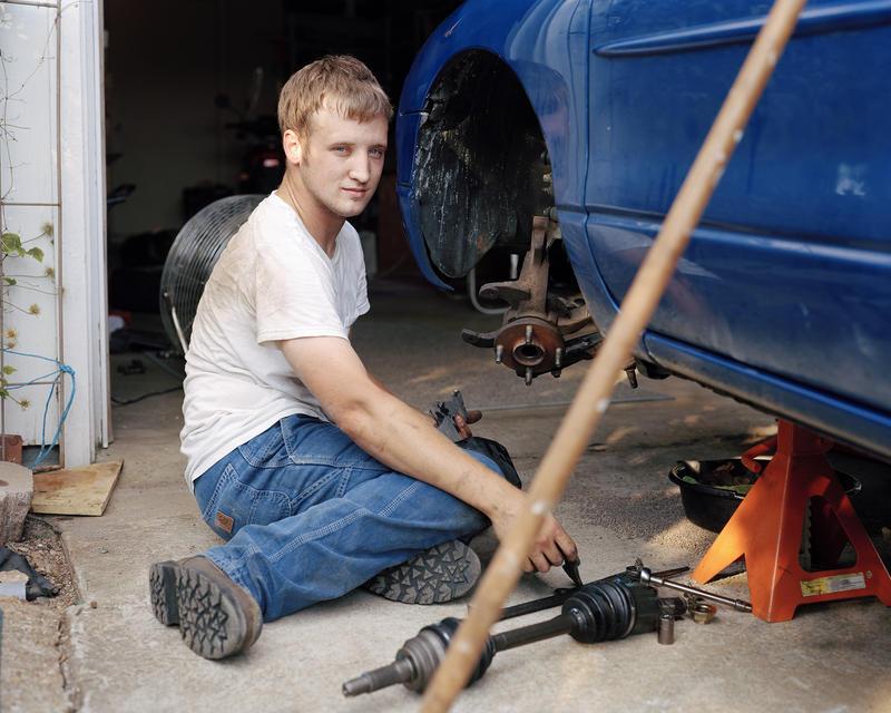 Jesse Holloway, 23, repairs his car in Park Hills. He carpools 75 miles to work in Saint Louis.