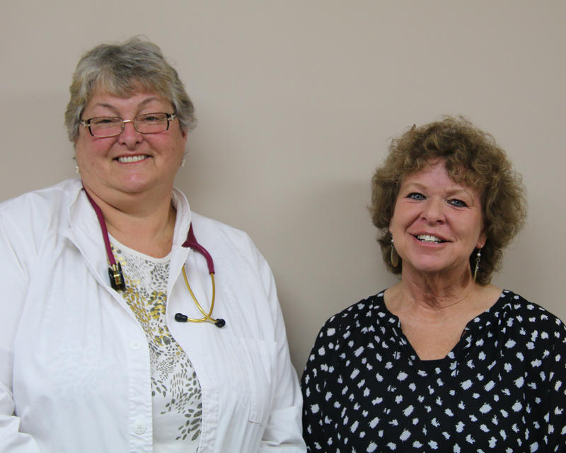 Susie McGee, left, wears a white lab coat and a red stereoscope. She stands next to Bev Borgeson, in a black and white spotted blouse. They both smile into the camera.