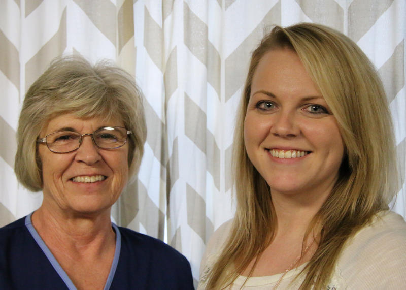 Patty McClendon, left, wears a blue scrubs top and wears glasses. Deborah Baker, right, has long blonde hair and wears an off-white blouse. They both smile into the camera.
