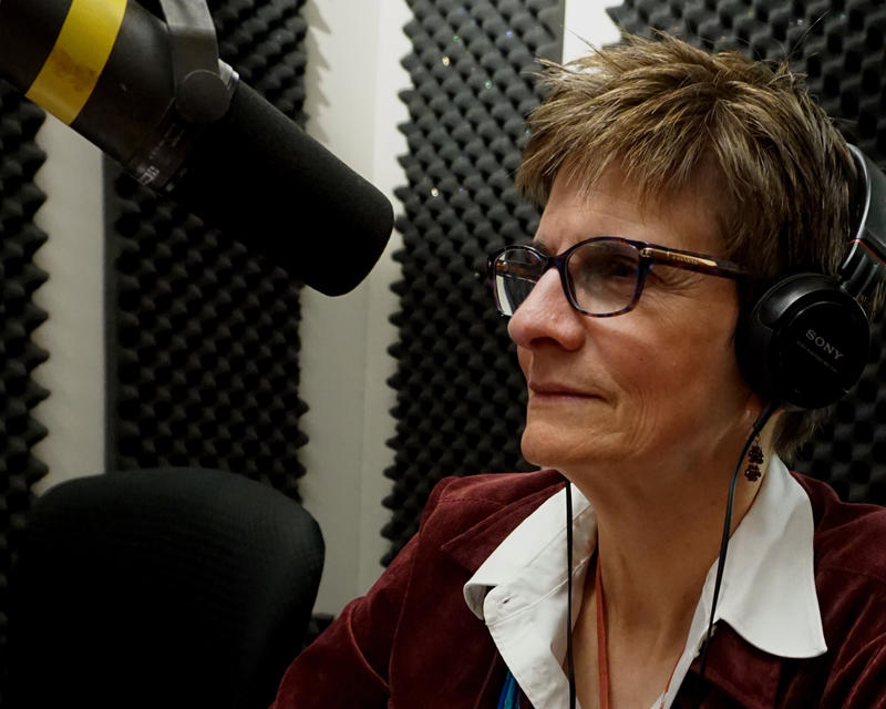 Heather Harlan sits in a radio booth. She sits at a microphone and wears black-rimmed glasses and a red, velvet blazer.