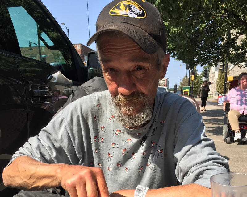Robert Nickles wears a grey sweatshirt and has a medium gray beard. He also has on a black Mizzou ball cap and looks into the camera.