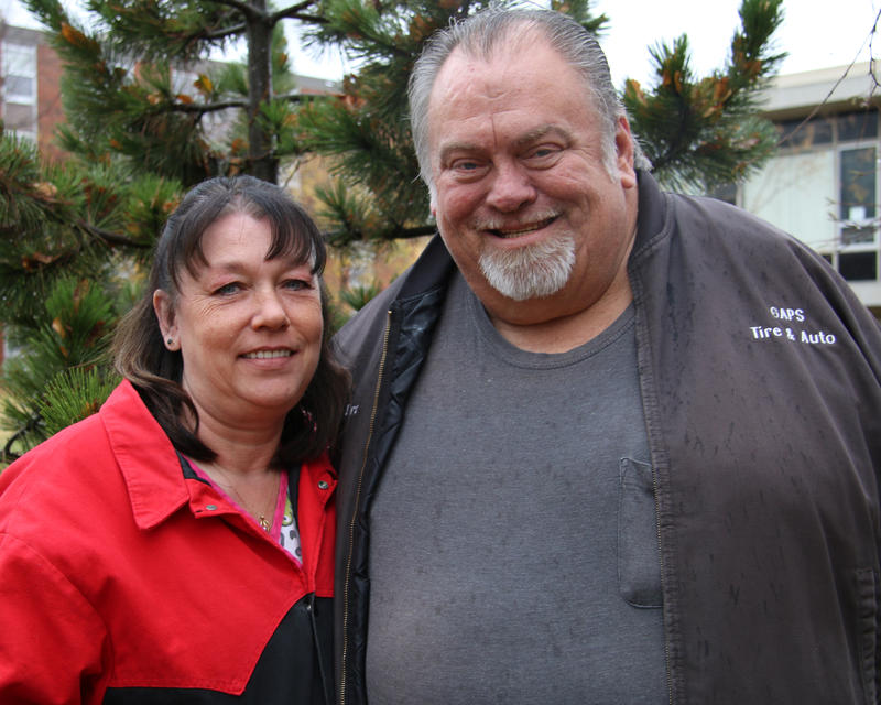 Teresa Graham, left, has long dark hair. She wears a black and red coat. Frankie Graham, right, has short gray hair and a trimmed gray beard. He wears a gray shirt and darker gray jacket.