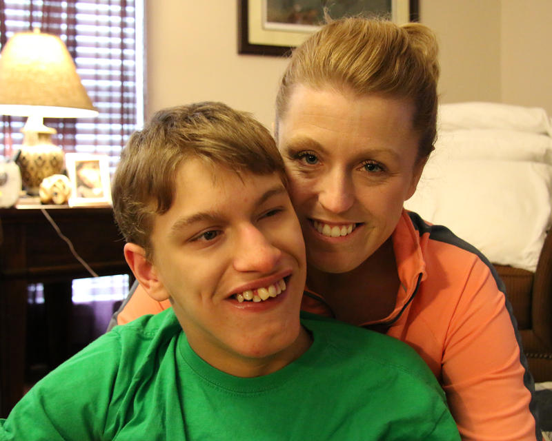 Jennifer Simmons, right, wears an orange jacket. She sits behind her son, Hunter, who wears a green shirt. They both have the same blonde hair and are smiling.