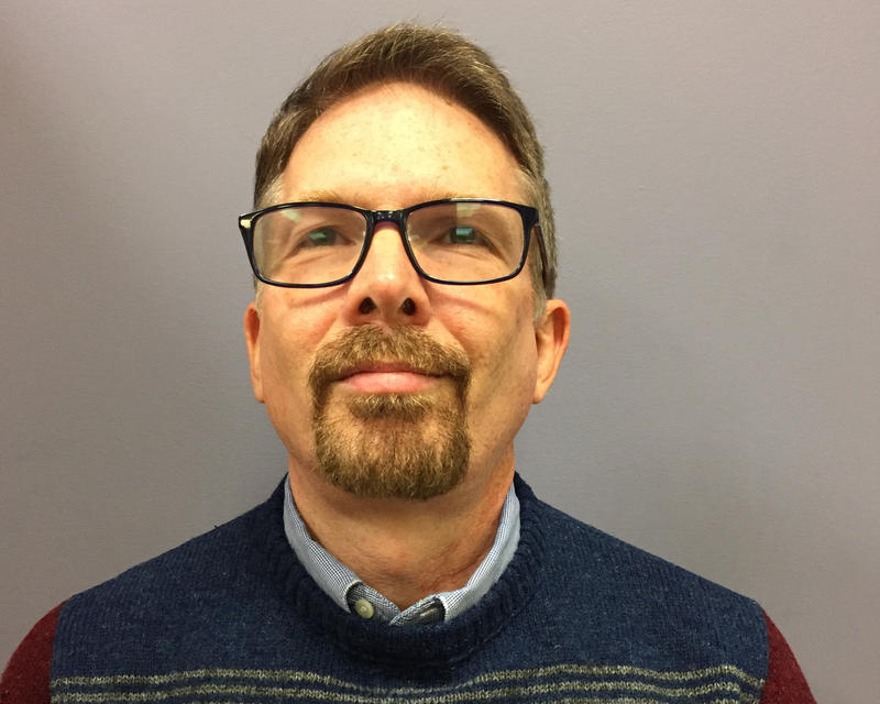 Jim Jantz looks into the camera. He has a goatee, wears glasses and a multi-colored sweater.