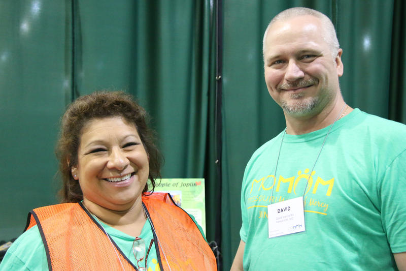 Debbie Vance, left, smiles into the camera and wears a green MOMOM shirt and an orange vest. Her husband, David Vance, also wears a green MOMOM shirt and smiles into the camera.